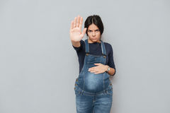 Serious pregnant lady make stop gesture. Image of serious pregnant lady standing over grey background and make stop gesture. Looking at camera Royalty Free Stock Image