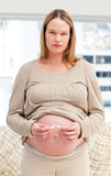 Serious pregnant woman breaking a cigarette Stock Photo