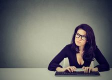 Serious preoccupied young woman sitting at desk typing on keyboard of a desktop. Serious preoccupied woman sitting at desk typing on keyboard of a desktop royalty free stock image