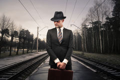 Serious presence. Man in suit and briefcase on the train tracks Stock Photo