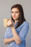 Serious pretty brunette holding cup of coffee Royalty Free Stock Images
