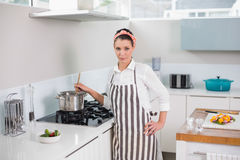 Serious pretty woman with apron cooking Stock Image