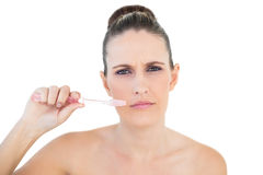Serious pretty woman brushing her teeth Royalty Free Stock Photography