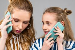 Serious pretty woman having important phone call while staying with her sister. Discussing daily news. Serious pretty women having important phone call while royalty free stock images