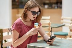 Serious pretty young European female with bobbed hairstyle, wears shades, downloads photos in internet, uses modern smart phone fo. R online communication, eats stock image