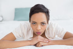Serious pretty young woman relaxing in bed Stock Photos