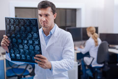 Serious professional doctor working in the oncology department. Diagnostic study. Serious professional male doctor standing in the staffroom and examining the X Stock Images