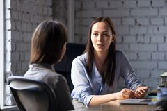 Serious professional female advisor consulting client at meeting. Talking having business conversation or making offer, insurer giving advice, mentor teaching royalty free stock photos