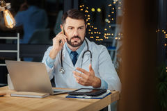 Serious professional physician putting a phone to his ear Royalty Free Stock Photography