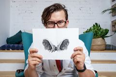 Serious professional psychologist showing paper with Rorschach inkblot. royalty free stock photos
