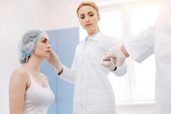 Serious professional surgeon taking a scalpel. Plastic surgery operation. Serious professional female surgeon standing in front of her patient and taking a Stock Photo
