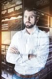 Serious programmer standing with his arms crossed and thinking. Thoughtful programmer. Calm attentive serious programmer looking concentrated while standing with Stock Photography