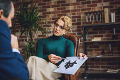 Serious psychologist showing inkblot on paper Royalty Free Stock Photo