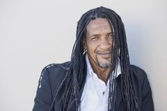 Portrait of adult strong black men with long dreadlocks and blue eyes. Serious pumped up man in a classic style - white shirt, blazer, jeans. This Dominican man Stock Image