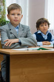 Serious pupils. Boys sit at school desks at school Royalty Free Stock Images