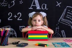 Serious and puzzled schoolgirl sitting at the desk with a pile of books under the chin, surrounded with school supplies. Chalkboard as a background royalty free stock images