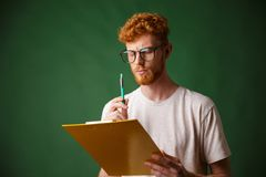 Serious readhead bearded man in white tshirt holding folder and. Pen, over green background Royalty Free Stock Photos