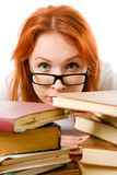 Serious red-haired girl in glasses with books. Royalty Free Stock Photo