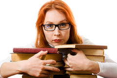 Serious red-haired girl in glasses with books. Royalty Free Stock Images