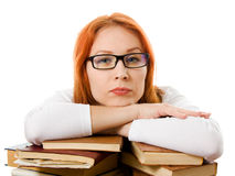 Serious red-haired girl in glasses with books. Stock Photos