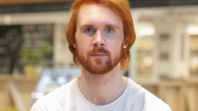 Serious Redhead Beard Man Looking at Camera in Cafe royalty free stock photography