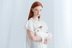 Serious redhead woman holding rabbit Stock Photo