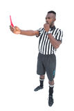 Serious referee showing red card blowing whistle Royalty Free Stock Photos
