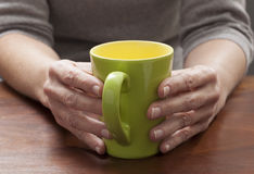 Serious reflection with focus on green coffee mug on slow mornings or for a comfortable break Stock Images