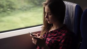 Serious, relaxed young girl sitting in the train near the window. Travelling by modern train. Long haired girl is. Scrolling or typing on her mobile phone stock video footage