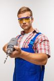 Serious repairman with drill Royalty Free Stock Photos