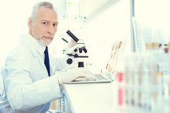 Serious researcher working on microscope and laptop. Daily routine. Waist up shot of a male lab worker looking into the camera while browsing his laptop and Royalty Free Stock Photos