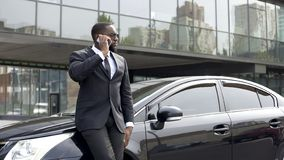 Serious rich man in expensive business suit talking over phone in big city royalty free stock photo