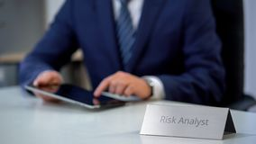 Serious risk analyst working on tablet computer, counting new project chances. Stock photo stock photography