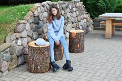 Serious or sad teenage girl. Wearing jeans, black boots, gray sweater and glasses sitting on wooden bench on pavement and stone wall background outdoors in yard royalty free stock images
