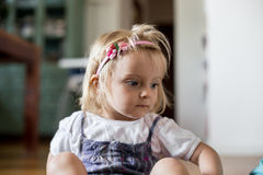 Serious sad or thinking young baby caucasian blonde girl wearing headband portrait at home Stock Photo