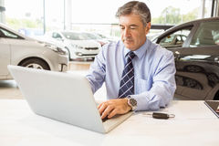 Serious salesman behind his desk Stock Photography