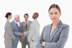 Serious saleswoman with arms folded and colleagues behind her Royalty Free Stock Photography