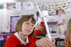 Serious school girl looking at model wind turbine in classroom Royalty Free Stock Images