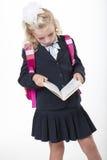 Serious school girl reads a book Royalty Free Stock Photos