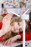 Serious school girl spinning model wind turbine in classroom Stock Images
