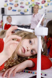 Serious school girl spinning model wind turbine in classroom Royalty Free Stock Photos