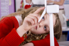 Serious school girl spinning model wind turbine in classroom Stock Photo