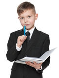 Serious schoolboy in black suit with a notebook Royalty Free Stock Photos
