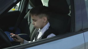 Serious schoolboy is opening the door of the car and sitting down into the car. stock video footage
