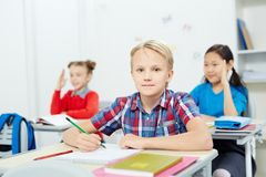 Schoolboy. Serious schoolboy with pencil looking at camera by desk while drawing at lesson Stock Photography