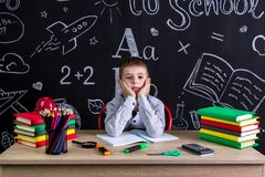 Serious schoolboy sitting on the desk with books, school supplies, with both arms under the cheecks.  stock images