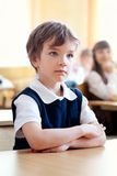 Serious schoolboy sitting at desk, classroom Royalty Free Stock Photography