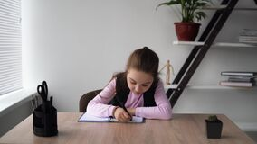 Serious schoolgirl 7s teen does her math tutor's homework by writing down the solution in a workbook. Problems of