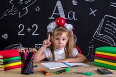 Serious schoolgirl sitting at the desk with books, school supplies, with a red apple on the top of her head, pointing royalty free stock images