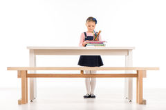 Serious schoolgirl standing at desk. And looking on books on white Stock Photos